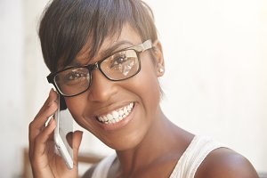 Close up portrait of happy dark-skinned woman with short pixie haircut wearing glasses, having phone conversation with cheerful look, smiling, showing her white teeth while talking to her boyfriend