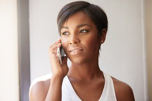 Indoor portrait of attractive young dark skinned African woman, using cell phone for ordering pizza for dinner, looking interested, smiling, looking through the window. Female having a phone talk