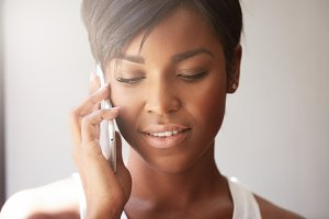 Close up portrait of attractive young female with healthy skin and short hair wearing casual top, making phone calls, talking to her boyfriend using smart phone, smiling, showing ultra-white teeth