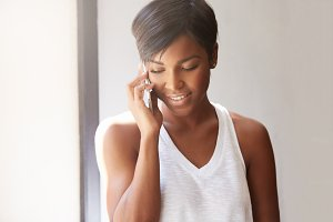Isolated headshot of beuatiful young brunette African woman talking on mobile phone, inviting her friends to her place, smiling, looking down. Pretty woman having a phone conversation indoors