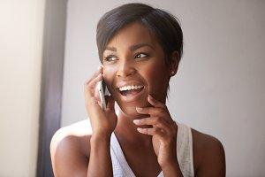 Young attractive African woman with short haircut talking on cell phone to her friend, looking cheerful, joyful and happy, sitting at the window, touching her chin. Human emotions and feelings