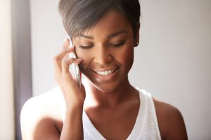 Portrait of young good-looking African woman with cute smile, talking on the phone with her little daughter, smiling, looking happy and touched, sun light covering her shoulders through the window
