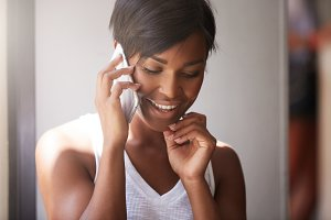 Close up portrait of beautiful dark skinned woman with healthy skin talking on cell phone with her man, smiling, looking happy, shy, and embarassed, touching her cheek, against white wall background