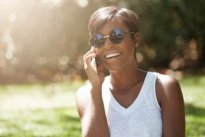 Close up portrait of dark skinned female laughing at a joke while having a phone conversation, enjoying summer sunny day in the city park, wearing stylish sunglasses, looking carefree and happy