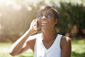 Half profile of beautiful young woman wearing casual white top and stylish shades laughing while talking on cell phone with happy look and mouth wide open, having a picnic in the park on sunny day