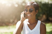 People, technology and communication concept. Headshot of cute African American young woman with short hairstyle wearing hipster shades, smiling while speaking on cell phone in the public garden