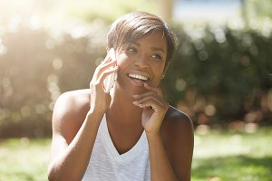 Close up portrait of beautiful dark skinned woman with short hairstyle, talking on cell phone, smiling and laughing with shy and happy expression, touching her face, against green park background