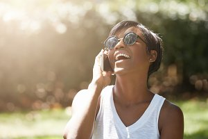 Human face expressions and emotions. Fashionable young dark-skinned female wearing stylish sunglasses having a nice phone talk, smiling, laughing with mouth wide open relaxing in the urban park