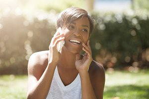 Young attractive African woman with short haircut talking on cell phone to her friend, looking happy, sitting on the grass in the city park, touching her chin. Human face expressions and emotions
