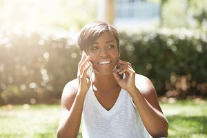Cute brunette woman with athletic body wearing white top, making phone calls while waiting for her friends in the city park. African female using electronic device against the public garden background