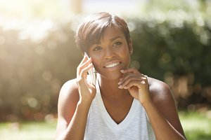 Portrait of charming African female with short hairstyle sitting on the grass, talking on mobile phone, smiling, touching her chin with thoughtful concentrated look, against urban park background