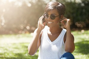 Headshot of stylish young woman with short pixie haircut wearing round shades making phone calls, smiling and flirting while having a conversation with her boyfriend, sitting on the green grass