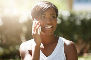 Close up shot of African American student girl with short hairstyle talking on mobile phone with happy excited look while having a picnic with her friends in the public garden on sunny summer morning