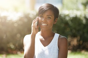 Close up portrait of successful dark-skinned businesswoman dressed casually talking on smart phone to her partners, smiling, joking, having a nice talk outdoors against public garden background
