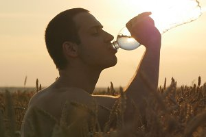 Young man drinking water from a plastic bottle in nature at wheat field. Boy having water break at sunset. The Sun in the Background. Silhouette of male profile