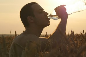 Young man drinking water from a plastic bottle in nature at wheat field. Guy having water break at sunset. The Sun in the Background. Silhouette of male profile