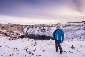 Woman in Kerid (or Kerith) volcanic crater lake on the touristic golden circle route in Iceland in winter