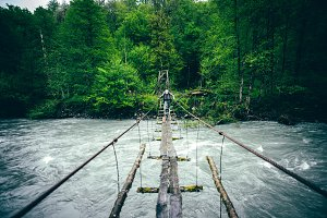 Man Traveler hiking on wooden bridge