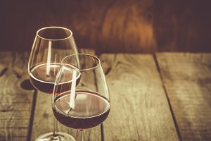 Glasses with red wine on rustic wood background