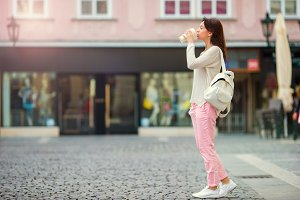 Happy young urban woman in european city. Caucasian tourist walking along the deserted streets of Europe.