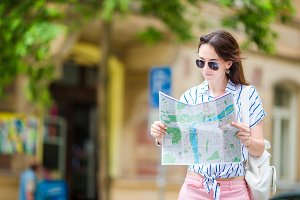 Happy young woman with a city map in Europe. Travel tourist woman with map in Prague outdoors during holidays in Europe.