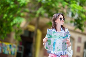 Happy young woman tourist with a city map outdoors. Travel caucasian girl with map outside during holidays in Europe.