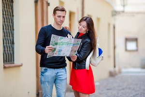 Young tourist couple traveling on holidays outdoors smiling happy. Caucasian family with city map in search of attractions