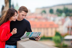 Young tourist couple traveling on holidays in Europe smiling happy. Caucasian family with city map in search of attractions