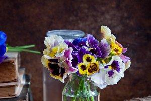 Pansies in glass bottles