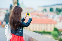 Tourist girl taking travel photos by famous attraction with smartphone on summer holidays. Young attractive tourist taking photo with mobile phone outdoors enjoying holidays travel destination in tourism and exploring concept
