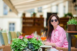 Portrait of young beautiful woman sitting in a cafe outdoor drinking tasty cocktail. Happy tourist enjoy european holidays at openair restaraunt