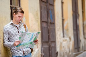 Man tourist with a city map and backpack in Europe street. Caucasian boy looking with map of European city in search of attractions.