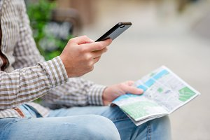 Closeup of male hands holding cellphone and city map outdoors on the street. Man using mobile smartphone to find famous attraction.