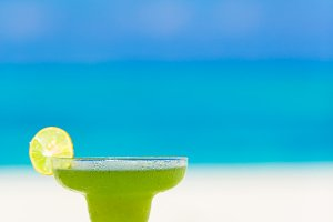 Green tasty cocktail on tropical white beach