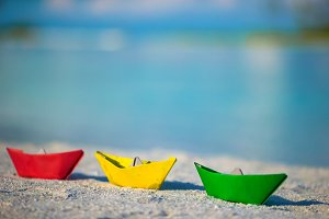 Colorful paper boats on tropical white beach outdoors