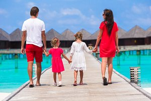 Beautiful family in red having fun on wooden jetty during summer vacation