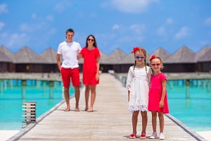 Young family of four have fun on wooden jetty during summer vacation