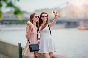 Young tourist friends traveling on holidays outdoors smiling happy. Caucasian girls making selfie background big bridge