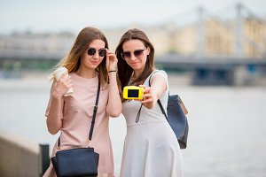 Caucasian girls making selfie background big bridge. Young tourist friends traveling on holidays outdoors smiling happy.