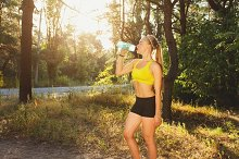Young sportswoman drinking water