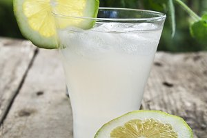 glass of lemonade on wooden background