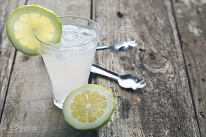 glass of lemonade on wooden background