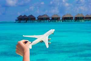 Small white toy airplane on tropical beach background water bungalow