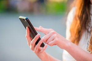 Closeup of female hands is holding cellphone outdoors on the street in evening lights. Woman using mobile smartphone.
