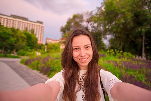 Young caucasian woman making selfie on attractions background outdoors. Happy girl enjoy her weekend in european city