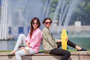 Portrait of happy young urban girls in european city. Caucasian tourists background the big fountain with skateboard outdoors