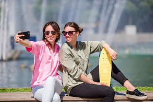 Caucasian girls making selfie background big fountain. Young tourist friends traveling on holidays outdoors smiling happy.