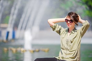 Portrait of happy young urban girl in european city. Caucasian tourist background the big fountain
