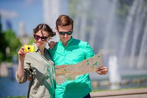 Young tourist friends traveling on holidays in Europe smiling happy. Girl taking photos in the park and man with city map in search of attractions