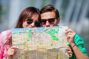 Young tourist friends traveling on holidays in Europe smiling happy. Closeup caucasian family with city map in search of attractions
